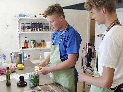 Kaks noormeest valmistavad kokkamisklubi raames köögis süüa.