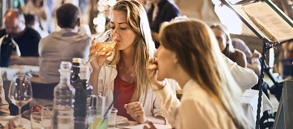 Naised söövad õhtul väljas õhtusööki ja naudivad aega.